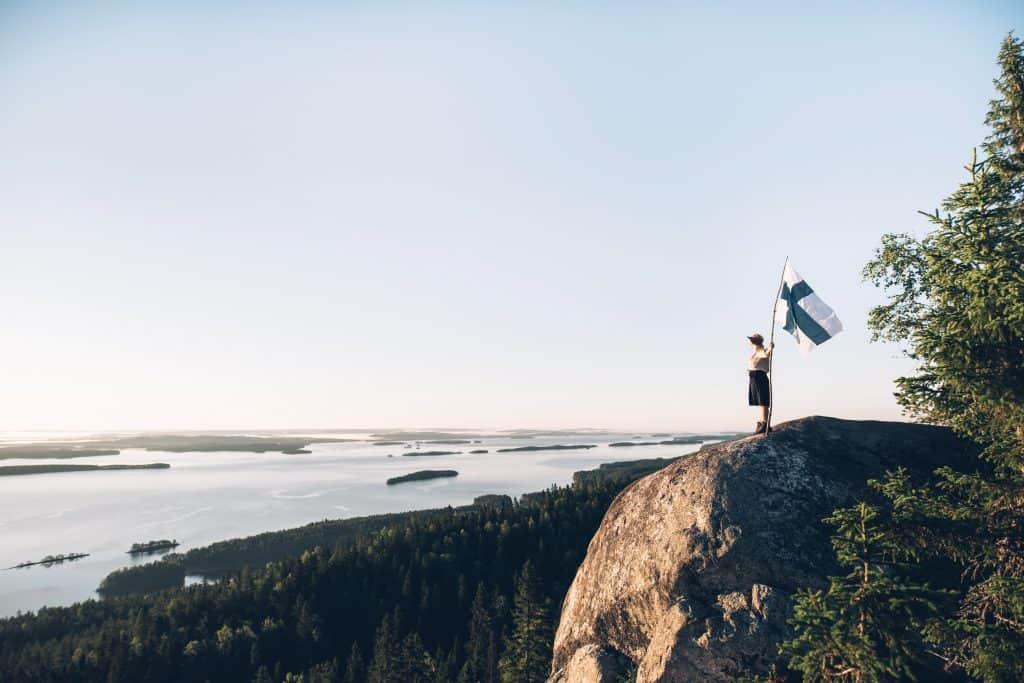 Henkilö Suomen lipun kanssa seisomassa kalliolla